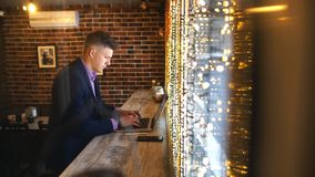 Un jeune homme d'affaires travaille dans un café avec un ordinateur portable banque de vidéos
