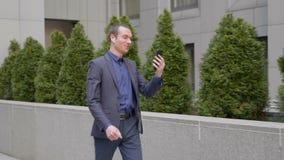 Un jeune homme d'affaires vient avec les écouteurs sans fil dans des ses oreilles et heureusement les entretiens à un faire app banque de vidéos