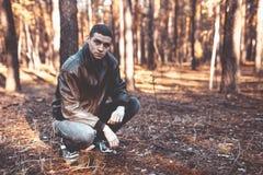 Un jeune homme d'aspect criminel dans une veste en cuir noire Photo stock