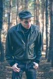 Un jeune homme d'aspect criminel dans une veste en cuir noire Photographie stock libre de droits