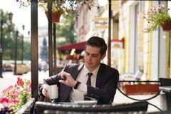 Un jeune homme dans un costume noir, une chemise blanche et un lien regarde l'horloge photo stock