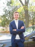 Un jeune homme dans un costume se tient près de la voiture avec ses bras pliés et le sourire outside photos stock