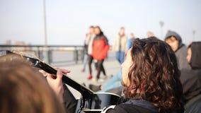 Un jeune homme dans des écouteurs jouant la guitare et chanter - des personnes passant par sur le bord de mer banque de vidéos
