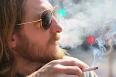 Un jeune homme dans des lunettes de soleil fume sur la rue Images libres de droits