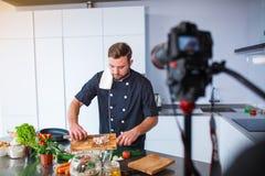 Un jeune homme dans la cuisine découpant des légumes en tranches, vous pouvez voir l'appareil-photo avec un trépied images stock