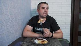 Un jeune homme dans la cuisine prend le petit déjeuner banque de vidéos