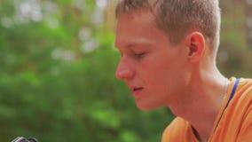 Un jeune homme dans la forêt prend une photo sur l'appareil-photo clips vidéos