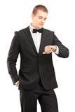 Un jeune homme dans le costume noir avec le noeud papillon regardant la montre-bracelet image libre de droits