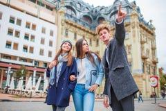 Un jeune homme dans un manteau sur la rue parlant aux filles Images stock