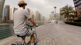 Un jeune homme dans un chapeau, un T-shirt rayé et des shorts montant son vélo sur la promenade parmi les gratte-ciel et les yach banque de vidéos