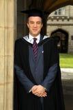 Un jeune homme dans une robe de graduation. Image stock