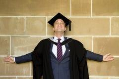 Un jeune homme dans une robe de graduation. Photographie stock libre de droits