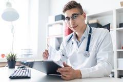 Un jeune homme dans une robe longue blanche se reposant à une table dans le bureau Il tient un stylo et un comprimé avec des docu image stock