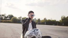 Un jeune homme dans une veste en cuir, se reposant sur sa moto, et lunettes de soleil de port banque de vidéos