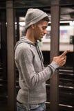 Un jeune, homme de couleur textote un ami tout en attendant le subw de NYC Images libres de droits