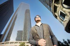 Un jeune homme de fantaisie descendant la rue parmi des gratte-ciel dans a Photos stock