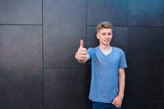 Un jeune homme de sourire dans un T-shirt montre des pouces sur un fond gris de mur L'ado l'aiment Photographie stock libre de droits