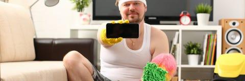 Un jeune homme de sourire tient un smartphone photographie stock libre de droits