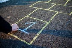Un jeune homme dessine le jeu de marelle sur l'asphalte Bons humeur et ressort en Russie Un homme barbu rappelle son enfance images stock