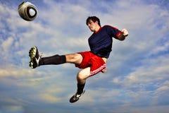 Un jeune homme donne un coup de pied un entre le ciel et la terre de soccerball Photo stock