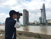 Un jeune homme employant DSLR pour prendre des photos Photos stock