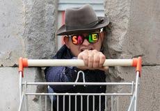 Un jeune homme en chapeau et verres avec la vente d'inscription s'élève par le mur en béton cassé Un homme tient un panier de image stock