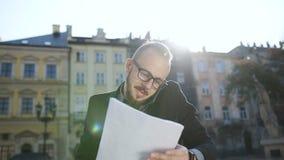 Un jeune homme en ses verres parlant au téléphone et écrivant des documents banque de vidéos
