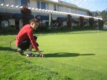 Un jeune homme essaye à l'herbe dense de pelouse sur le golf Image libre de droits