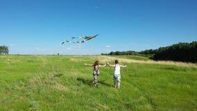Un jeune homme et une fille courant à travers le champ Couplez le cerf-volant de vol de lancement Vacances de famille banque de vidéos