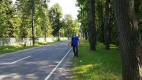 Un jeune homme faisant de l'auto-stop du côté de la route Accrocher une conduite banque de vidéos