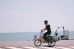 Un jeune homme faisant du vélo pour surfer à la mer image libre de droits