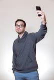 Un jeune homme fait un autoportrait avec son téléphone portable Photo stock