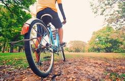 Un jeune homme fait un cycle dans le coucher du soleil en parc Photographie stock