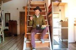 Un jeune homme heureux dans un chapeau tient un avion et la carte se prépare au voyage dans un appartement, une caméra pend l'AR photos stock