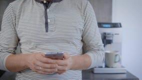 Un jeune homme heureux utilise un téléphone intelligent dans une cuisine à la maison clips vidéos