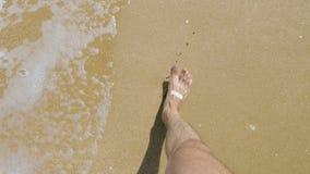 Un jeune homme marchant le long de la plage sablonneuse clips vidéos