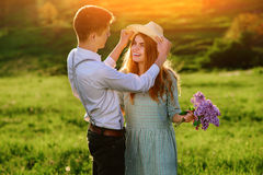 Un jeune homme marche avec son amie en parc, l'homme tenant le chapeau du ` s de fille Photos stock