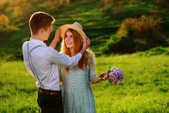 Un jeune homme marche avec son amie en parc, l'homme tenant le chapeau du ` s de fille Images libres de droits