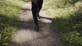 Un jeune homme marche le long d'un chemin forestier clips vidéos
