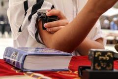 Un jeune homme mettant un Tefillin juif sur sa main Images libres de droits
