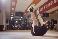 Un jeune homme, homme moyen ordinaire, ABS d'exercice, bras s'est prolongé haut en air Photographie stock