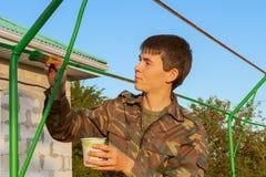 Un jeune homme, un homme occupé dans la réparation, peignant une construction métallique dans le jardin avant photos stock