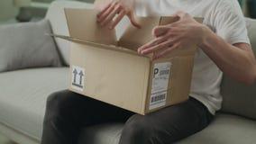 Un jeune homme ouvre un colis de carton sur le divan dans son salon banque de vidéos
