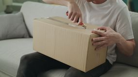 Un jeune homme ouvre un colis de carton sur le divan dans son salon clips vidéos