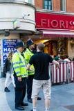 Un jeune homme parlant avec deux policiers de Londres photo stock