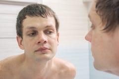 Un jeune homme rasé de près regarde dans le miroir photo libre de droits