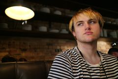 Un jeune homme regardant à partir de l'appareil-photo dans un restaurant Photos libres de droits