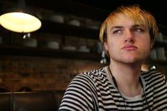 Un jeune homme regardant à partir de l'appareil-photo dans un restaurant avec la Co Photo libre de droits