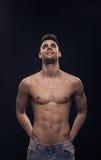 Un jeune homme regardant en haut, ABS convenable de corps sans chemise Photographie stock
