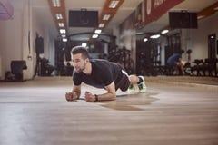 Un jeune homme, regardant loin, exercice de planche, plancher de gymnase, Photos libres de droits